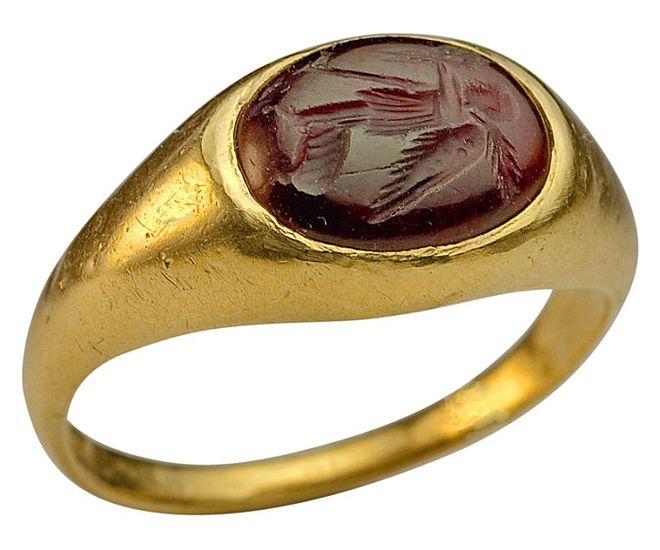Złoty pierścień zdobiony granatem zwyrzeźbionym wnim intaglio zwizerunkiem boga małżeństwa Hymena zczasów starożytnej Grecji