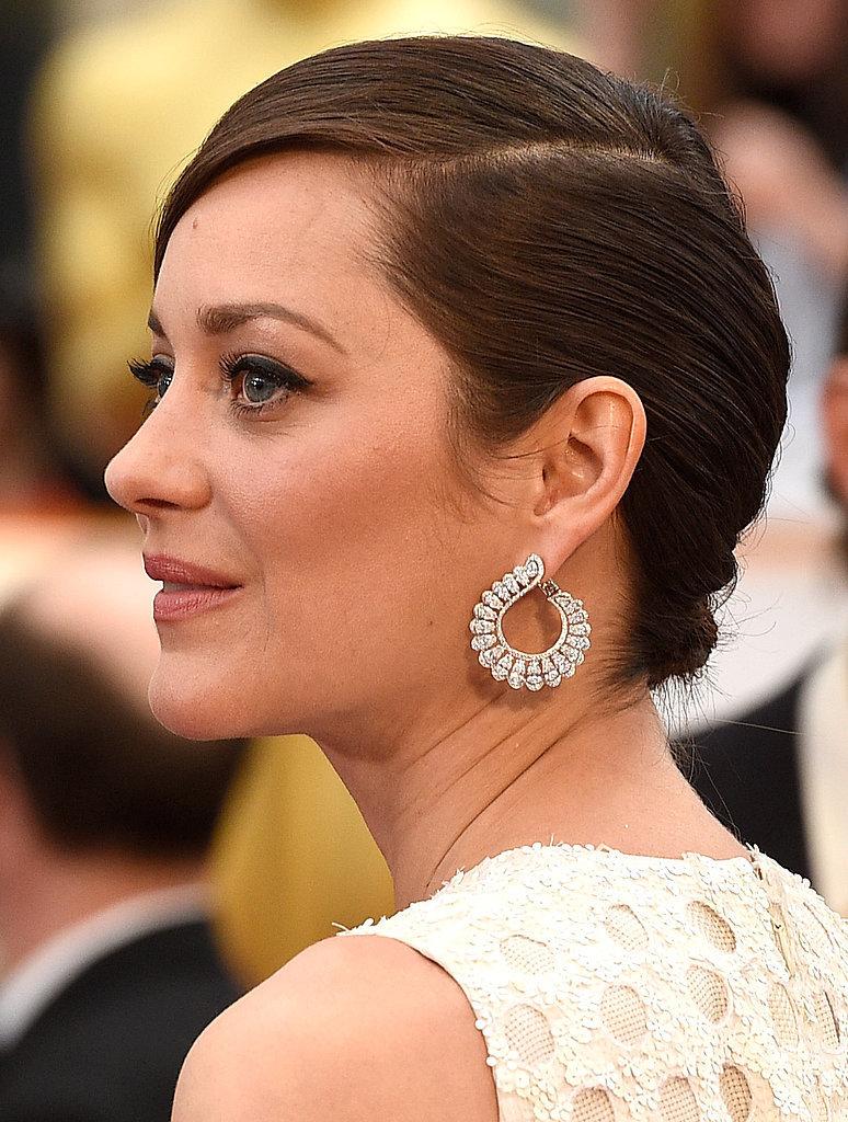 Marion Cotillard wdiamentowych kolczykach marki Chopard, które ciekawie korespondują zokrągłymi wycięciami wtkaninie sukni.