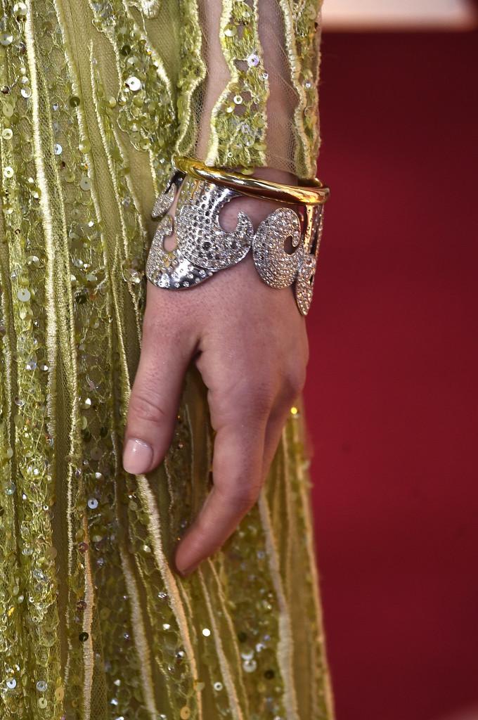 Zdobiona motywem wirów bransoleta cuff odTiffany & Co. nanadgarstku Emmy Stone, wydaje się wręcz stworzona dosukni odElie Saab, wyszywanej żółto-złotymi cekinami.